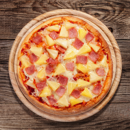 Hawaiian pizza on the old table. Banque d'images