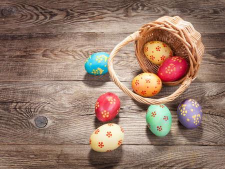 Easter eggs in basket of wooden boards.