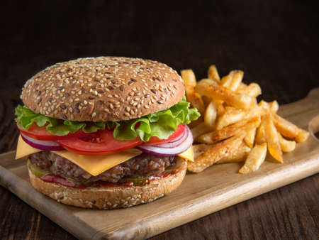 fresh tasty burger and potatoes on wooden board.