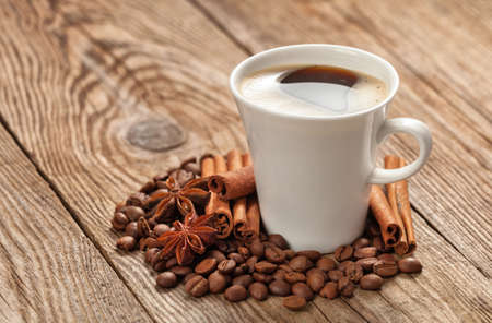 cup of coffee with coffee beans and spices anise star.