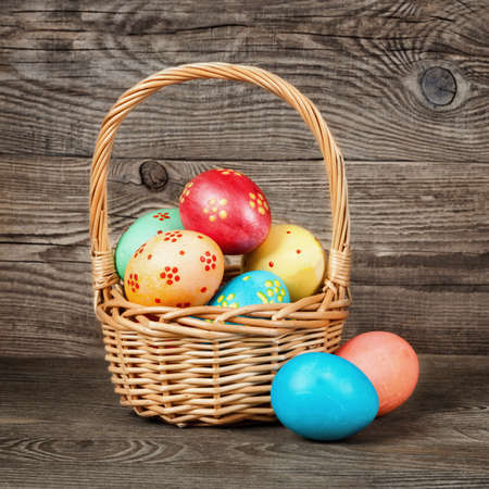 Easter eggs in the basket of wooden table.