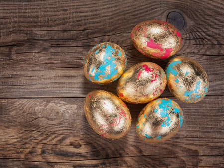 Golden Easter eggs on the old board. Фото со стока