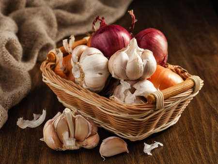 Onion and garlic in a basket on the table.