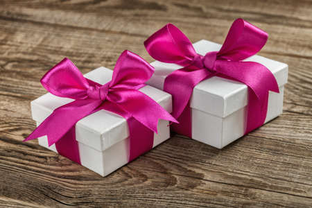 gift boxes with violet bow on wood board.