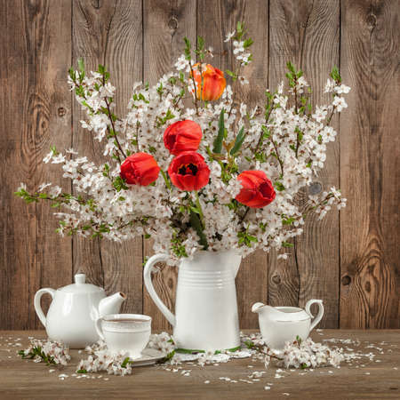 Tulips and cherry blossom on a decorated table.