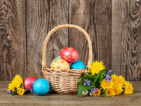 Easter eggs in the basket of wooden table Фото со стока