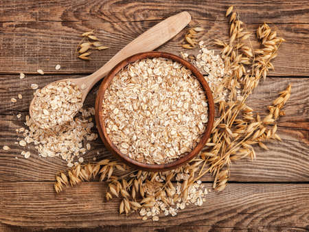 oatmeal in a bowl and spoon on the old board on top. Spikes of oats.