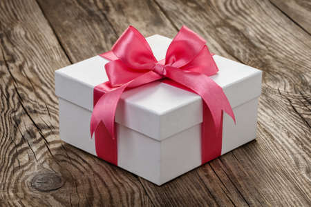 White gift box with a pink ribbon on the old board. Фото со стока