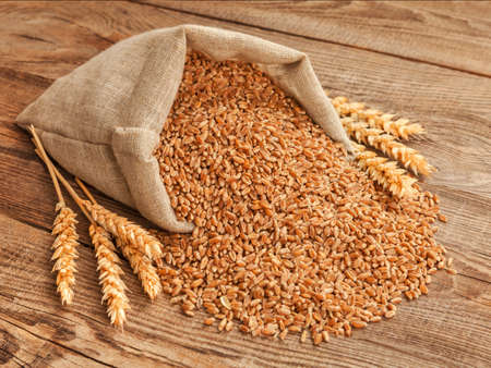 wheat grain in a bag and spikes on the table.