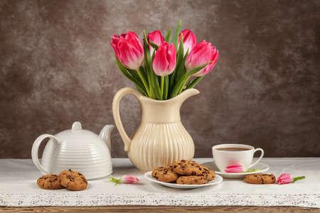 Tulips in a vase, tea, chocolates on the board. Фото со стока