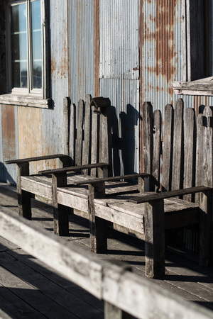 all weather: A weather worn wooden bench inviting all who pass a chance to relax while others shop in the quaint country cider store behind it.