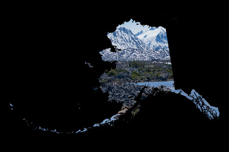 ample: Framed in a dark, black background, a silhouette of Alaska is filled with a beautiful, scenic image of snow covered mountains, rugged terrain,  and a beautiful lake. Ample room for text  copy. Stock Photo
