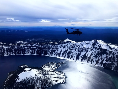 An attack helicopter flies over a mountain lake in Oregon. Stock Photo