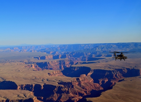 An attack helicopter flies over a large canyon in Arizona. Stock Photo