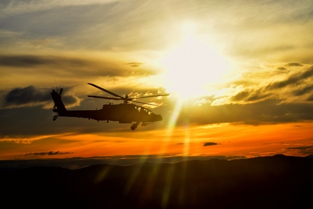 An attack helicopter flies through the sunset in the Iraq desert.