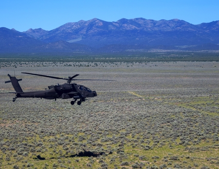 An Attack Helicopter flies low over the desert.