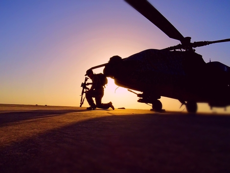 Crew Chief kneeling in front of an attack helicopter ready to take off for mission over Iraq