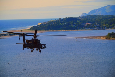 Attack helicopter flying over the ocean on Oregons West Coast.