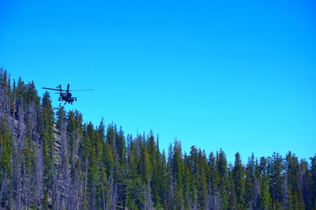 AH-64 Apache Attack Helicopter Climbs a Wooded Mountain in Colorado Stock Photo