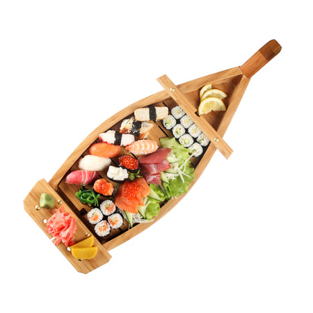 Set of sushi on wooden stand in the form of the boat isolated on white
