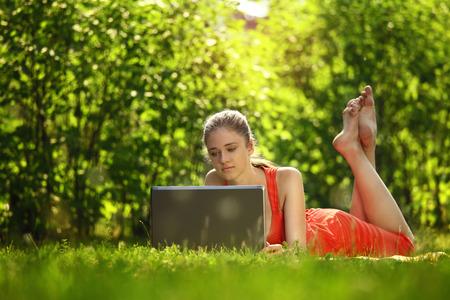 Junge Frau mit Laptop auf grünem Gras zu parken