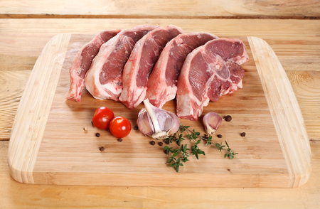 Raw meat lamb, entrecote on the bone, on a wooden board