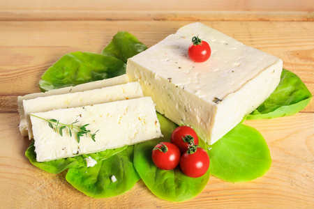 Fresh solid cream cheese on wooden board with fresh herbs