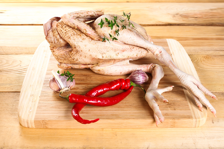 carcass: Fresh raw chicken carcass on wooden board with pepper