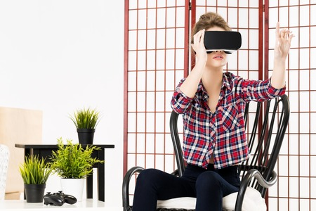 gesticulating: Happy woman getting experience using VR-headset glasses of virtual reality at home much gesticulating hands