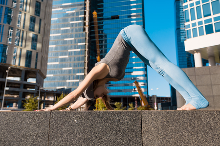 Young girl doing yoga outdoors in a city on the background of skyscrapers