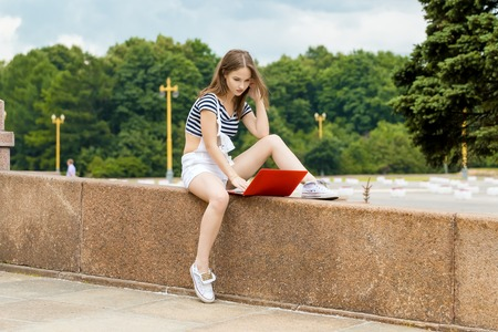 Young woman with a laptop sitting on the stairs, near the university Stock Photo