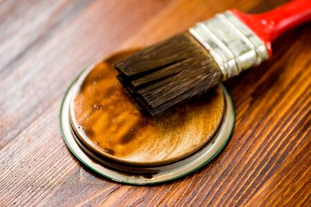 varnished: Half painted wooden surface. Deep brown color. Varnishind natural wood with paint brush