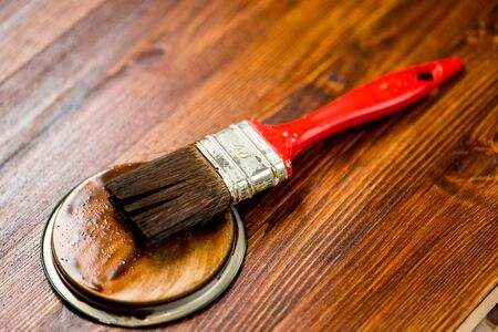 wooden surface: Half painted wooden surface. Deep brown color. Varnishind natural wood with paint brush
