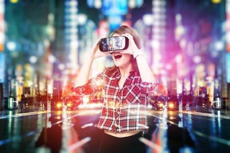 이중 노출, 어린 소녀 점점 경험 VR 헤드셋은 가상 현실에있는, 증강 현실 안경을 사용하고 있습니다. 밤에 도시에서 스톡 콘텐츠