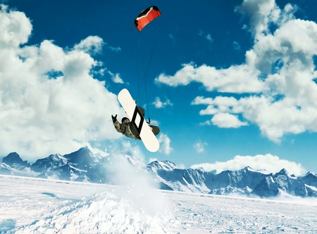 kiting: Young men, ride snowboarding on frozen lake in the mountains, in the rays of the rising sun, in winter, on vacation Stock Photo