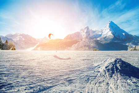 kiting: Young men, skiing on frozen lake in the mountains, in the rays of the rising sun, in winter, on vacation