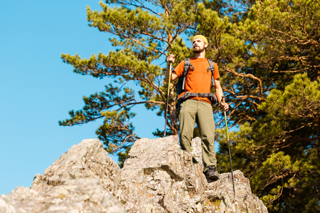Young male with beard is traveling through the mountain, a tourist with a rucksack standing on rock hill while enjoying nature view, summer holidays in the mountains.