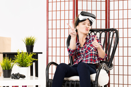 HI: Happy woman getting experience using VR-headset glasses of virtual reality at home much gesticulating hands