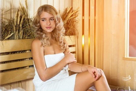 sauna nackt: Young beautiful woman relaxing in the Finnish sauna wrapped in towel