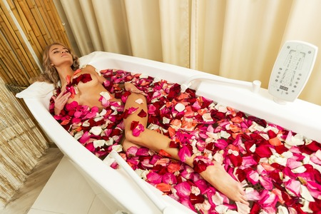 Young beautiful girl receives milk bath with rose petals in spa salon Stock Photo