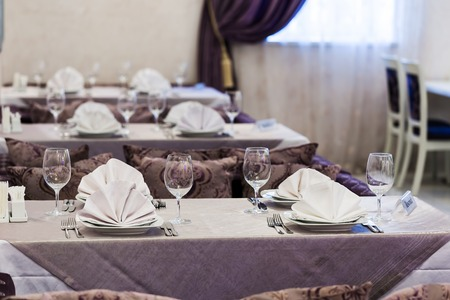 Empty glasses and dishes set in an empty interior new luxury restaurant with covered tables and crockery