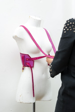 Young girl fashion designer, makes handmade swordbelt, harness in his studio
