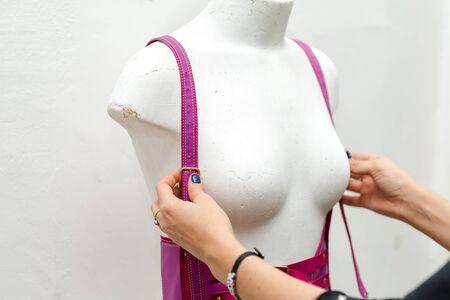 Young girl fashion designer, makes handmade swordbelt, harness in his studio