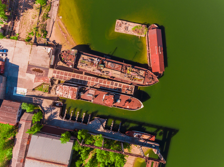 Aerial view, two old, rusty barges, moored at the pier on river