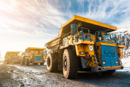 Large quarry dump truck. Loading the rock in dumper. Loading coal into body truck. Production useful minerals. Mining truck mining machinery, to transport coal from open-pit as the Coal Production. Stock Photo