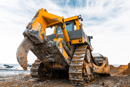 Yellow excavator in career moves overburden. Bulldozer combs the ground, with the bright sun and nice blue sky in the background