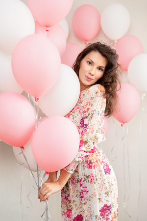 Beautiful young girl in dress with balloons on birthday. Portrait of cute woman with multicolored balloon. Cute brunette girl in the studio with balls filled Stok Fotoğraf