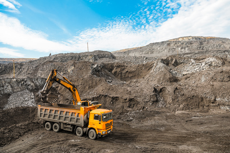 Large quarry dump truck. Loading the rock in dumper. Loading coal into body truck. Production useful minerals. Mining truck mining machinery, to transport coal from open-pit as the coal production. Banque d'images