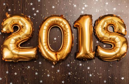 Bright metallic gold balloons figures 2018, Christmas, New Year Balloon with glitter stars on dark wood table background