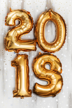Bright metallic gold balloons figures 2018, Christmas, New Year Balloon with glitter stars on white wood table background